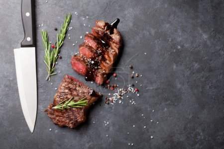 Photo pour Steak de bœuf tranché grillé au romarin sur table en pierre - image libre de droit