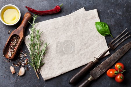Photo for Chili, garlic, basil leaf, olive oil, kitchen towel, old fork and knife, cherry tomatoes, rosemary, salt and pepper over stone table, top view. Herbs and spices cooking ingredients - Royalty Free Image