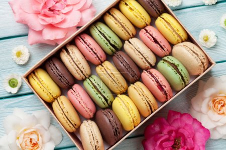 Photo for Colorful Sweet macarons in box on wooden table - Royalty Free Image