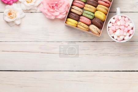 Photo for Colorful macaroons and marshmallow on wooden table. Sweet macarons in gift box. Top view with copy space for your text - Royalty Free Image