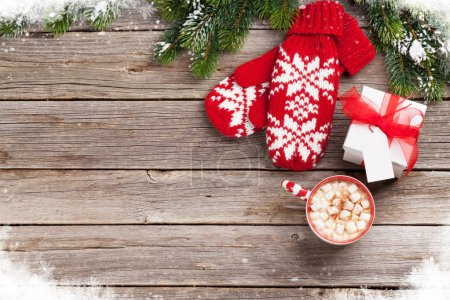 Photo for Christmas background with fir tree branch, mittens, hot chocolate and marshmallow on wooden table. Top view with copy space - Royalty Free Image