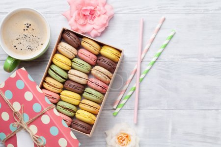 Photo for Colorful macaroons in gift box and coffee cup on wooden table - Royalty Free Image