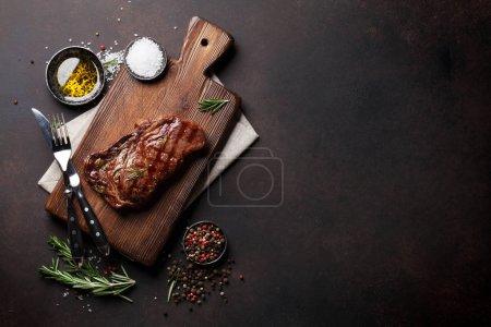 Photo pour Steak de bœuf côtelé grillé, herbes et épices. Vue du dessus avec espace de copie pour votre texte - image libre de droit