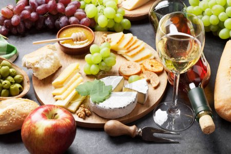 White wine, grapes, bread and cheese on stone tabl...