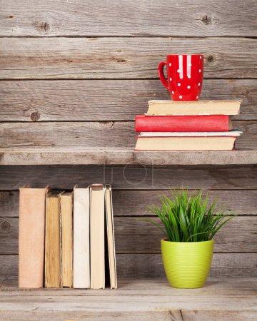 Photo pour Livres anciens sur étagères en bois, tasse à café et plante avec espace vide - image libre de droit