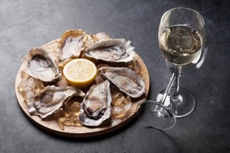 Photo for Opened oysters, ice and lemon on board and white wine over stone table - Royalty Free Image