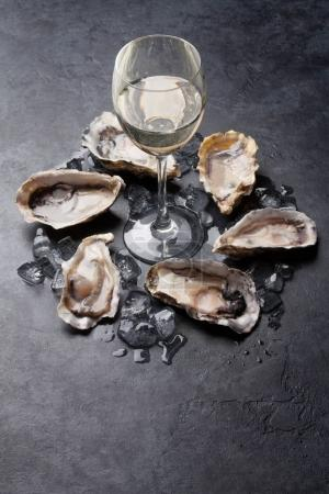 Photo for Opened oysters, ice, lemon and white wine glass on stone table - Royalty Free Image