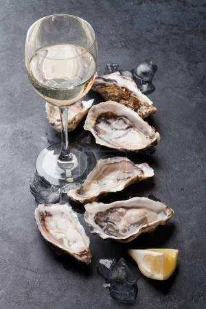 Photo for Opened oysters, ice and lemon with white wine over stone table - Royalty Free Image
