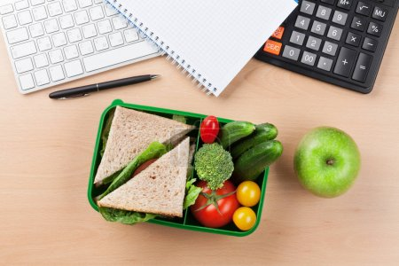 Office supplies and lunch box with vegetables