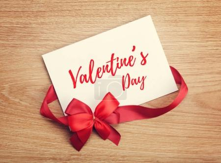 Valentine's day blank gift card and red ribbon with bow on wooden background