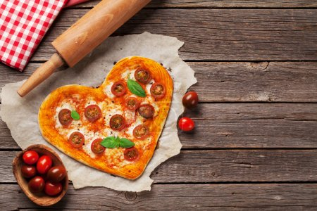 herzförmige Pizza mit Tomaten und Mozzarella. Valentinstag-Grußkarte. Ansicht von oben mit Platz