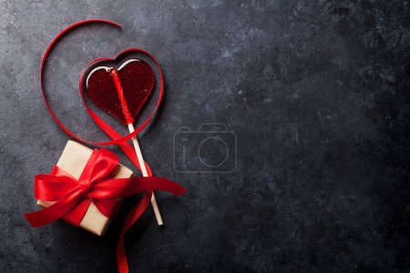 Valentines day greeting card. Candy heart and gift box on stone table. Top view with copy space