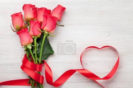 Photo for Valentines day greeting card with red roses and heart shaped ribbon on wooden background. Top view with space - Royalty Free Image