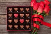 """Постер, картина, фотообои """"Валентинка с красной розы и сердца в форме шоколад на деревянных фоне. Вид сверху"""""""