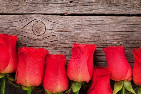 Valentines day greeting card with red roses on wooden table. Top view with space for your greetings