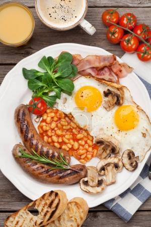 Photo for English breakfast. Fried eggs, sausages, bacon, beans, toasts, tomatoes, orange juice and coffee cup on wooden table. Top view - Royalty Free Image