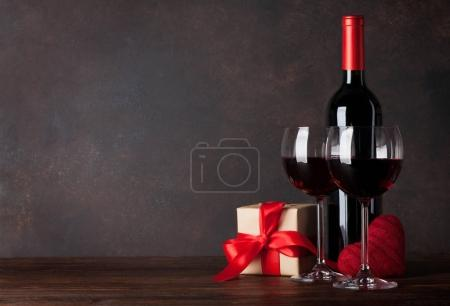 Valentines day greeting card with red wine, decorative heart and gift box on wooden table. With chalkboard