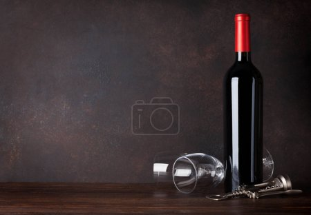 Red wine bottle and glasses in front of blackboard wall. With copy space