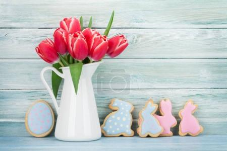 Red tulips bouquet in pitcher and gingerbread cookies in front of wooden wall.  Easter greeting card. With space