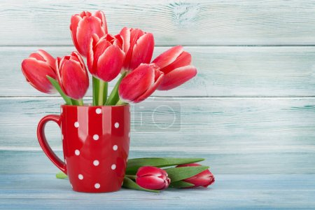 Red tulips bouquet in cup in front of blue wooden wall. Greeting card. With space