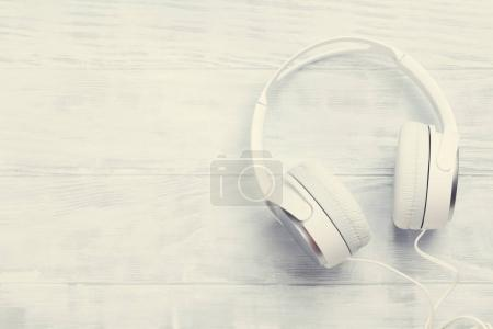 Headphones on white wooden table. Top view with copy space. Retro toned