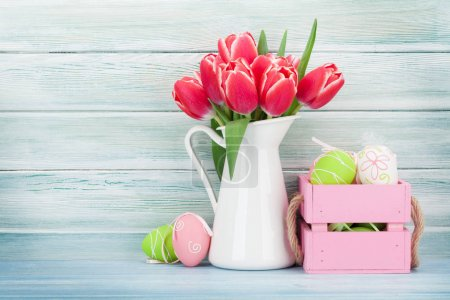 Red tulips and easter eggs in front of wooden wall. Easter greeting card with space