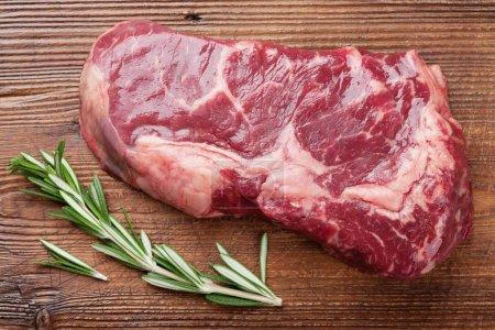Raw ribeye beef steak cooking with rosemary on cutting board