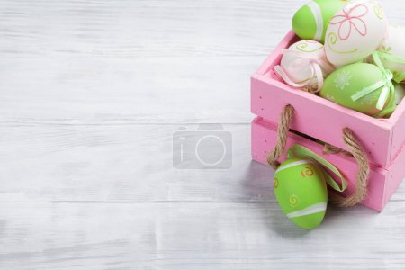 Easter eggs in box on wooden table. With space for your greetings