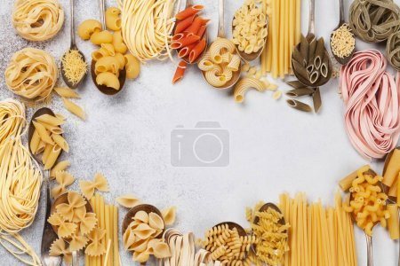 Various pasta on spoons over stone background. Cooking concept. Top view with space for your recipe
