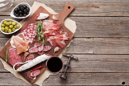 Photo for Meat antipasto platter and red wine on wooden table. Top view with copy space - Royalty Free Image