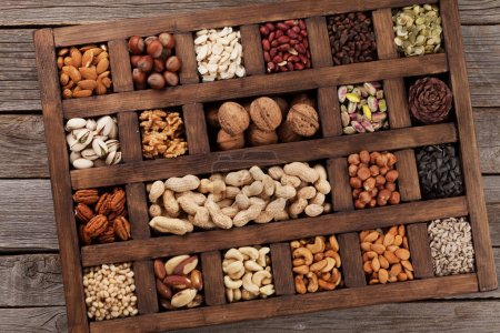 Various nuts selection: peanuts, hazelnuts, chestnuts, walnuts, pistachios and pecans in wooden box. Top view