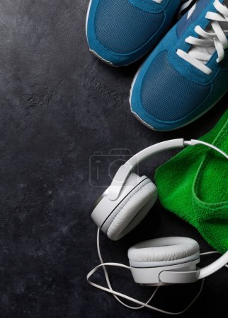 Fitness concept background with sneakers, headphones and towel. Top view with copy space