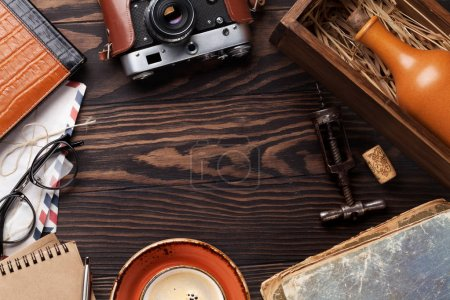 Retro table with vintage items. Camera, books, notepad, wine bottle and corkscrew, coffee cup. Top view with space for your text