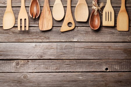Various cooking utensils over wooden kitchen table. Top view with space