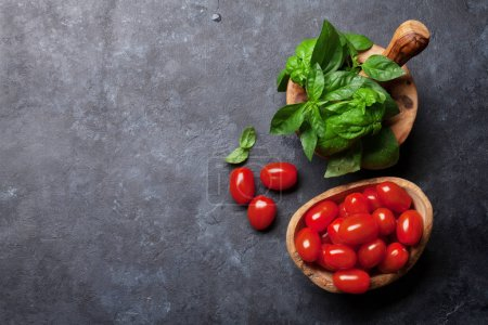 Italian cuisine. Basil and tomato cooking. Top view with space for your recipe