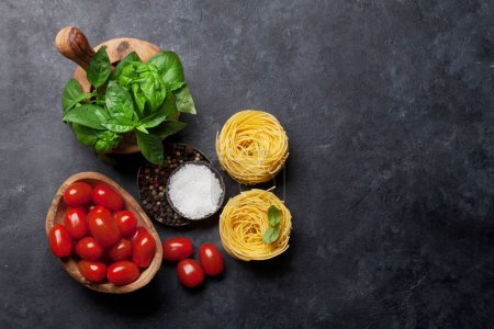 Photo for Italian cuisine. Basil, tomato, pasta and spices cooking. Top view with space for your recipe - Royalty Free Image