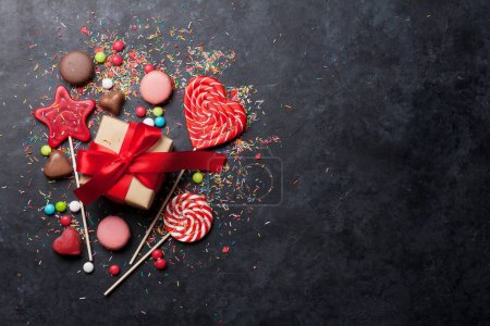 Colorful sweets. Lollipops, macaroons, candies and gift box. Top view with space for your text