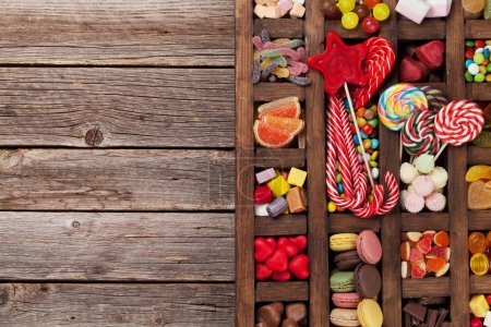 Colorful sweets box. Lollipops, macaroons, marshmallow, marmalade and candies. Top view with space for your greetings