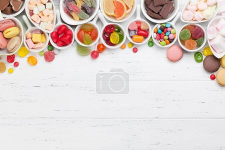 Colorful sweets. Lollipops, macaroons, marshmallow, marmalade, chocolate and candies. Top view with copy space