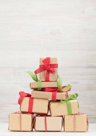Photo pour Carte de voeux de Noël avec diverses boîtes-cadeaux devant un mur en bois avec espace de copie pour vos salutations - image libre de droit