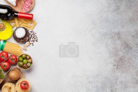 Photo for Italian cuisine food ingredients. Pasta, cheese, salami, olives and wine. Top view flat lay on stone table with copy space - Royalty Free Image