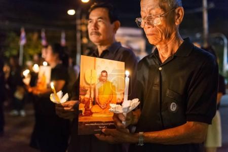 Thai people lighting candles and praying