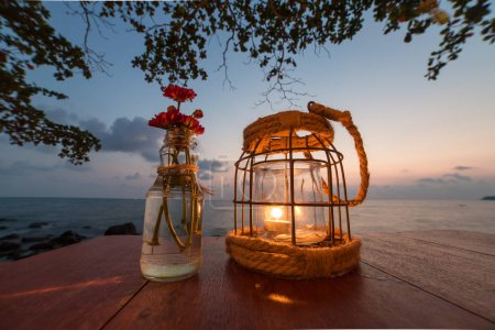 Candle on table at sunset