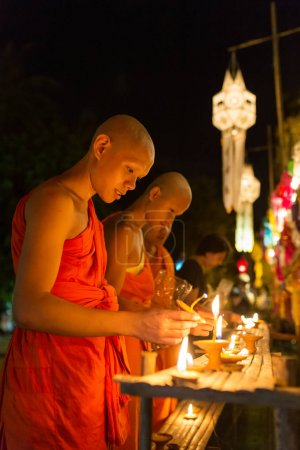 Chiang Mai, Thailand - November 13, 2016: Young Buddhist monks fire candles to the Buddha in Wat Phan Tao Temple during Yi Peng Festival in Thailand.