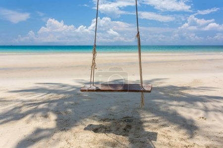 Wooden swing hanging on the beach on Koh Kood island in Thailand.
