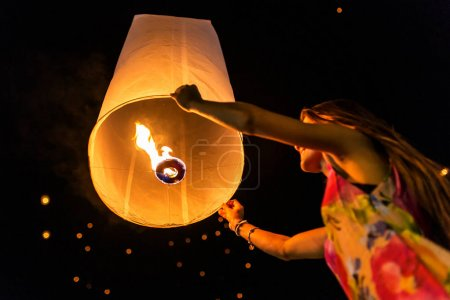 Unidentified woman release Khom Loi, the sky lanterns during Yee Peng festiva in Chiang Mai, Thailand.