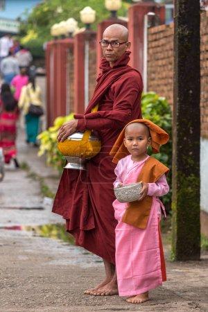 Kyaikhtiyo, Myanmar - October 16, 2016: Buddhist monk with a small novice girl collecting alms and offerings on the streets near the Kyaiktiyo pagoda or Golden rock, Myanmar.