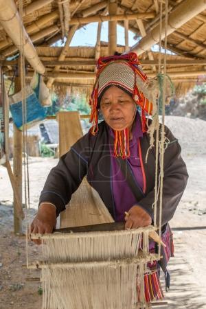 Chiang Rai, Thailand - February 8, 2017: Akha woman weaving fabrics in traditional way in Akha village, Northern Thailand