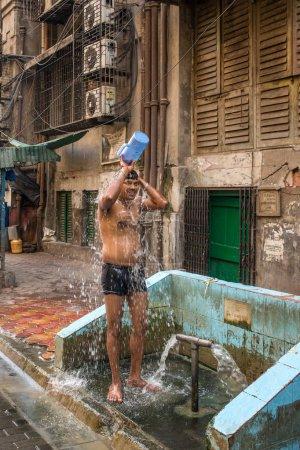 Mumbai, India - April 8, 2017: Indian man taking shower from bucket on streets of Mumbai, India