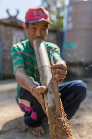 Chiang Rai, Thailand - February 8, 2017: Unidentified elderly Akha man is smoking traditional tobacco pipe in Akha hilltribe village in Northern Thailand